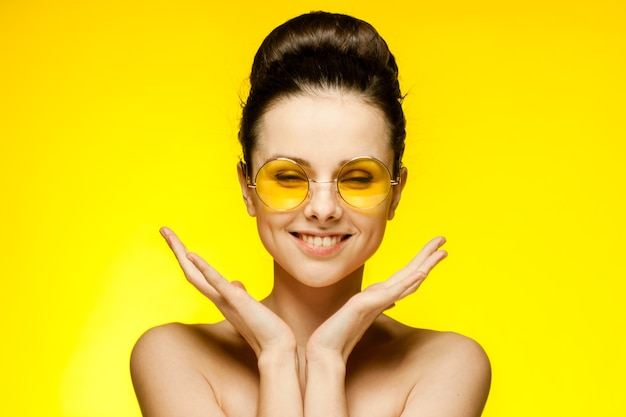 ファッションメガネをかけている裸の肩を持つ感情的な女性は、髪の黄色の背景を集めました