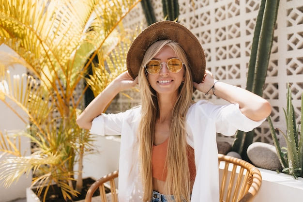 Emotional woman with blonde straight hair posing with eyes closed in resort restaurant. charming caucasian female model in brown hat smiling during photoshoot in cafe.
