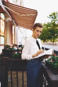 手に本を持つ感情的な女性白いシャツの肖像画モデルのトリミングされたビュー