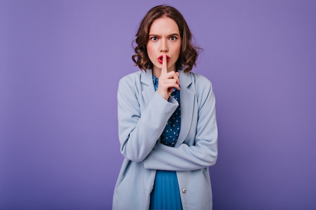 指で唇に触れる明るい化粧の感情的な女性。紫色の壁に立っている青いコートの魅力的な巻き毛の女の子。