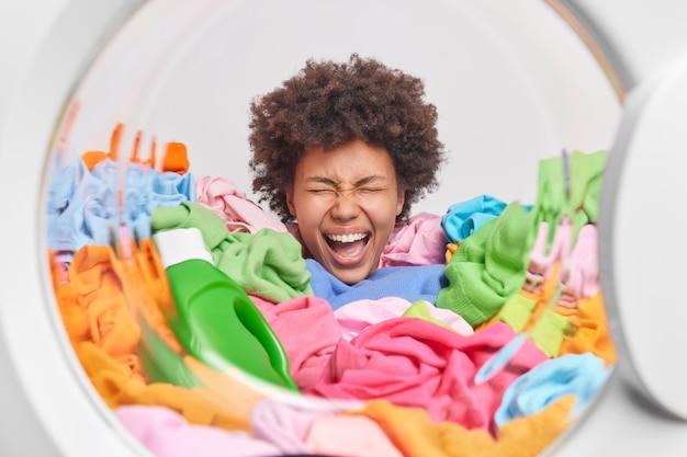 곱슬머리를 한 감정적인 여성은 세탁기 내부에서 세탁 포즈를 하느라 분주한 액체 가루 한 병과 함께 여러 가지 빛깔의 세탁물 더미에 머리를 꽂습니다.