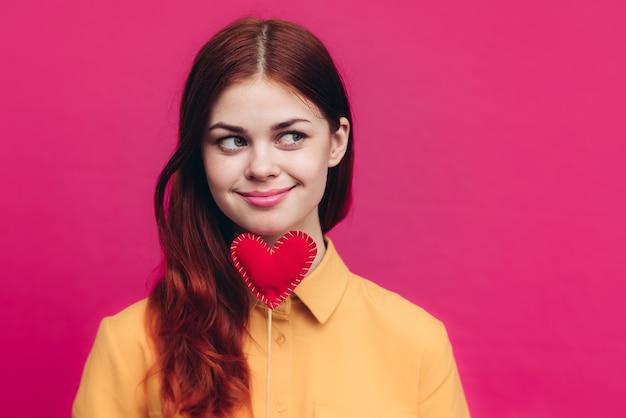 スティックにハートとピンクの背景に黄色のシャツと感情的な女性