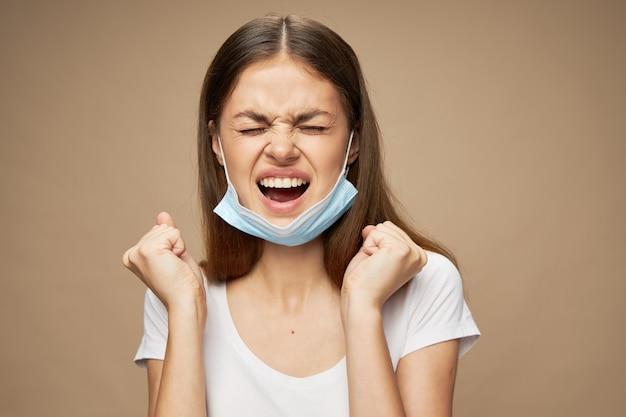 顔の攻撃性に医療用マスクを持つ感情的な女性が口を開き、拳で手