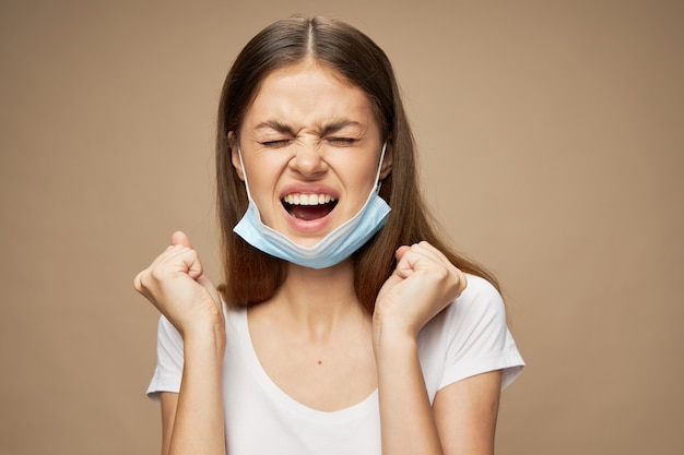 Эмоциональная женщина с медицинской маской на лице, стрессовая агрессия, открытый рот и руки в кулаке