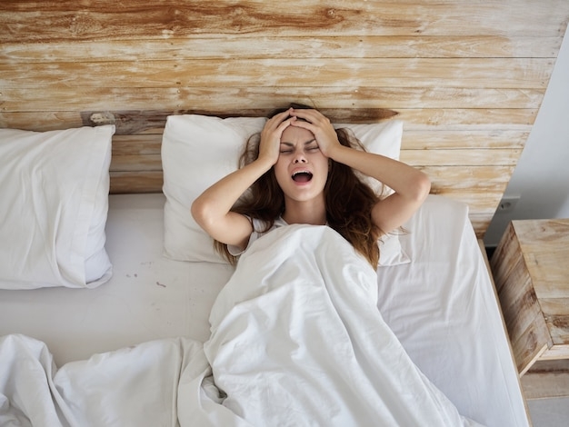 Emotional woman with open mouth hold hands on head while lying in bed top view