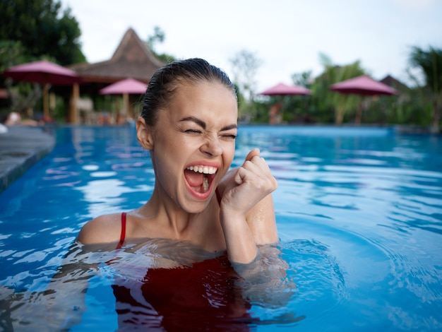 口を開けて感情的な女性はプールの赤い水着の自然で泳ぐ