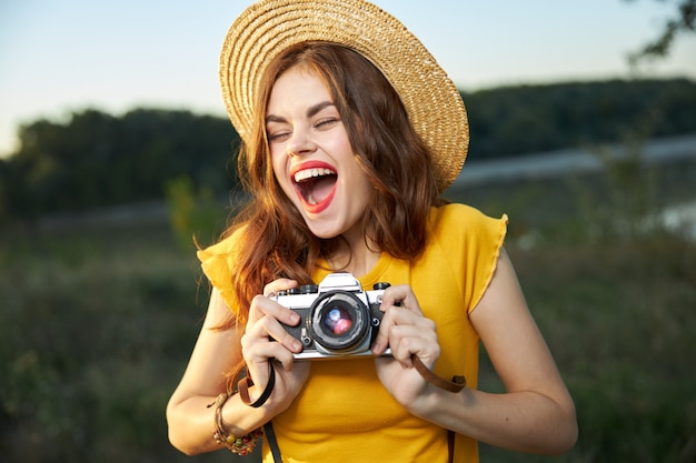 Эмоциональная женщина с открытым ртом с фотоаппаратом в руках на природе.
