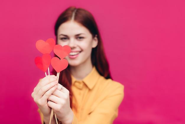 ピンクとバレンタインデーのスティックに紙のハートを持つ感情的な女性