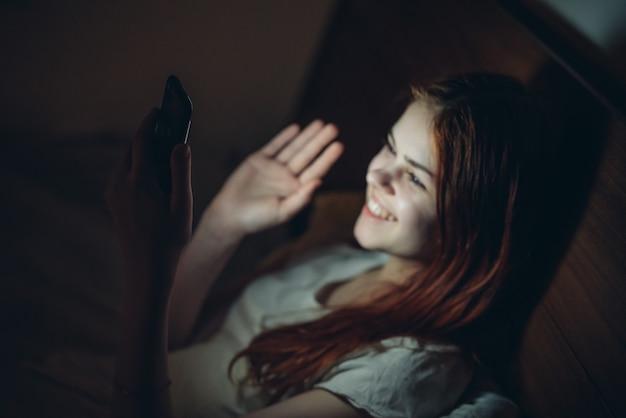 ベッド技術中毒で横たわっている夜に手に電話を持つ感情的な女性