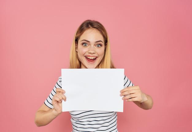 Эмоциональная женщина с белым листом бумаги на розовом обрезанном виде