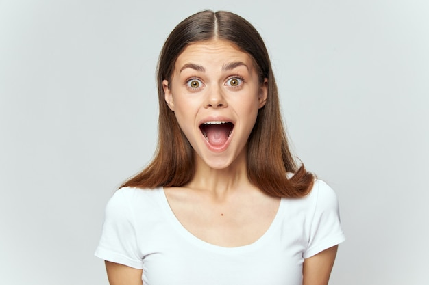 Emotional woman with wide open mouth in white t-shirt brunette