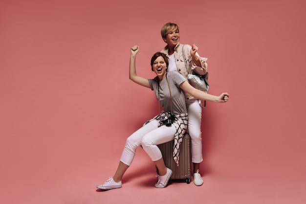 Эмоциональные женщины с короткой крутой прической в белых штанах, футболках и легких кроссовках смеются на розовом изолированном фоне.
