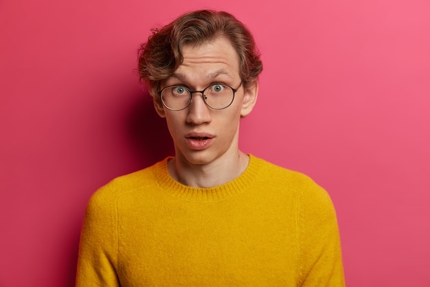 Emotional wondered male student finds out bad results of passed exam, cannot believe in failure, feels surprised hearing interesting rumor, gazes impressed , wears spectacles, yellow sweater