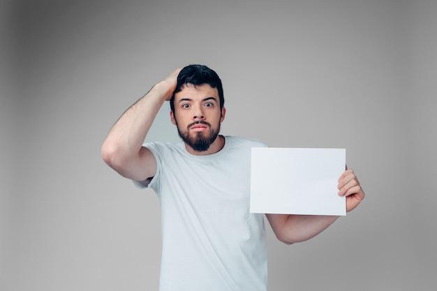 感情的な心配の男は手に空白のページを保持します。ひどく驚いた。