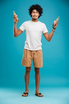Emotional young african curly man holding beer.