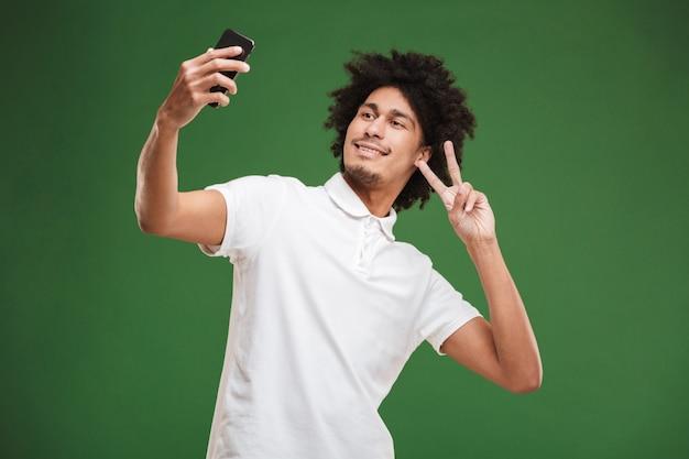 感情的な若いアフリカの巻き毛の男は、平和のジェスチャーを示す携帯電話でselfieを作ります。