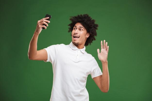 感情的な若いアフリカ巻き毛の男は、携帯電話でselfieを作る。