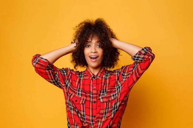Giovane posa africana emozionale della donna isolata sopra fondo arancio. volto a sorpresa. colpo dello studio