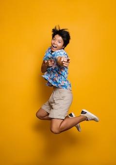 Эмоциональный молодой азиатский человек прыгает изолированный над указывая желтым космосом.