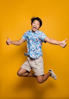 Эмоциональный молодой азиатский человек прыгает изолированно над желтым пространством, показывая большие пальцы руки вверх.