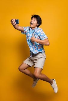 黄色い空間を飛び越えてジャンプする感情的な若いアジア人男性は、親指を立てて携帯電話で自分撮りをします。