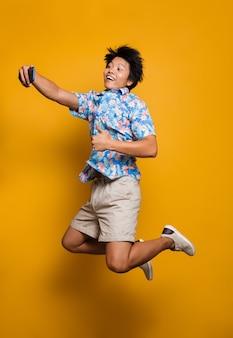 Эмоциональный молодой азиатский человек, прыгающий изолированно над желтым пространством, делает селфи по мобильному телефону с большими пальцами руки вверх.