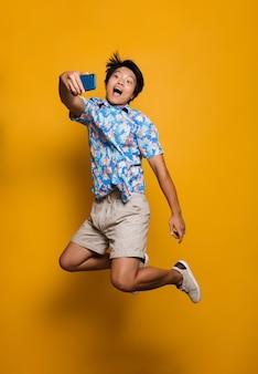 Эмоциональный молодой азиатский человек, прыгающий изолированно над желтым пространством, делает селфи по мобильному телефону.