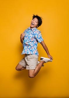 Эмоциональный молодой азиатский человек прыгает изолированным над желтым пространством.