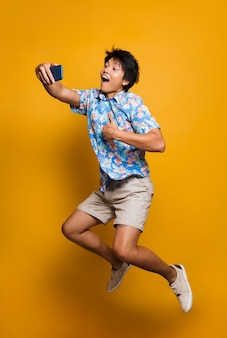 Emotional young asian man jumping isolated over yellow space take a selfie by mobile phone with thumbs up.