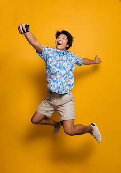 Emotional young asian man jumping isolated over yellow space take a selfie by mobile phone.