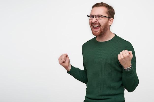 Эмоциональный молодой бородатый мужчина в очках с короткими каштановыми волосами, возбужденно глядя в сторону с широко открытым ртом и поднятыми руками, позирует
