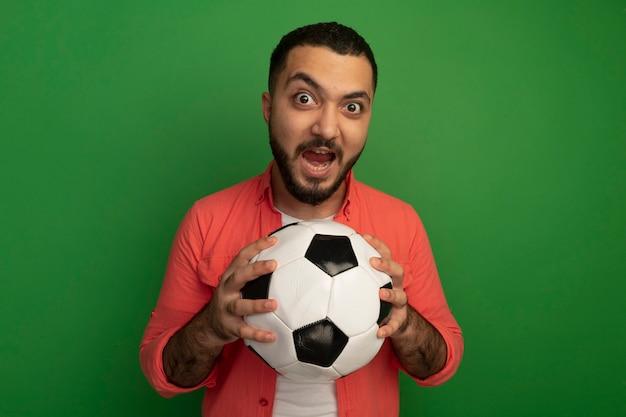 Emotivo giovane uomo barbuto in maglietta arancione tenendo il pallone da calcio guardando gridando in piedi sopra la parete verde