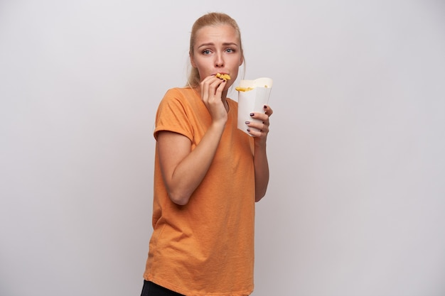 Emotional young blue-eyed blonde woman with ponytail hairstyle looking in front of her and eating french fries while standing over white background in orange t-shirt