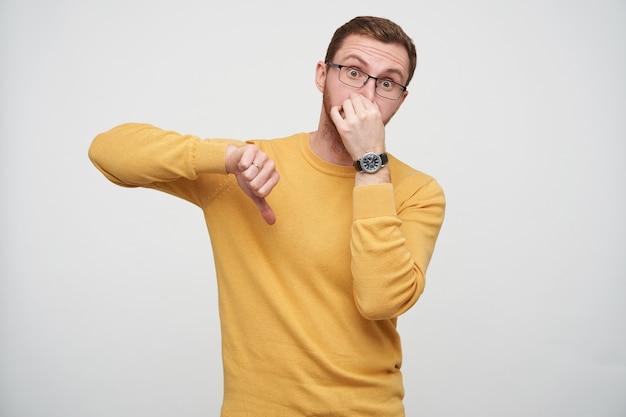 Эмоциональный молодой бородатый шатенка в очках и повседневном пуловере позирует, показывая пальцем вниз и прикрывая рот