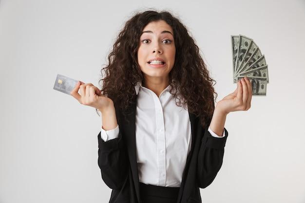 Эмоциональная молодая деловая женщина с кредитной картой и деньгами