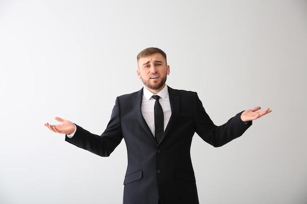 Эмоциональный молодой бизнесмен после ошибки на белом фоне