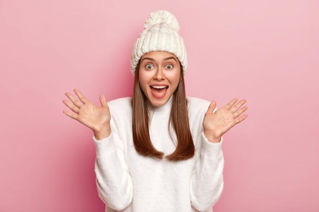 感情的な若い白人女性は、手のひらを上げ、口を開いたままにし、楽しんで、冬の白い服を着て、ピンクの背景の上にポーズをとります。