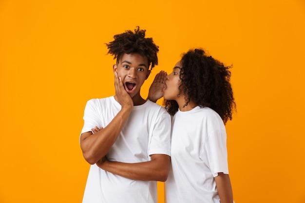감정적 인 젊은 귀여운 아프리카 커플 포즈 노란색 공간 험담에 고립 된 비밀을 말해.