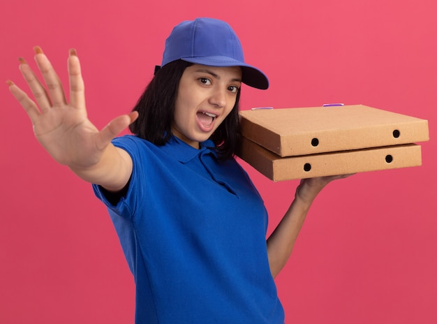 Эмоциональная молодая доставщица в синей униформе и кепке держит коробки для пиццы, делая жест с открытой ладонью, стоя над розовой стеной