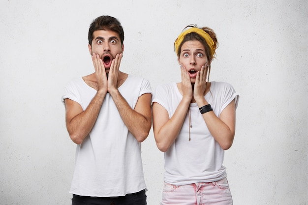 Эмоциональные молодые европейские мужчина и женщина смотрят в шоке и панике, держат рты широко открытыми и вытаращенными, удивленные неожиданной изумительной новостью, выглядящие в полном недоумении