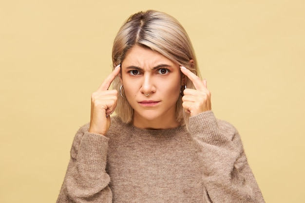 Emotional young female in sweater suffering from headache, having brain strain massaging temples with fingers, feeling frustrated with indignation, frowning, trying to think
