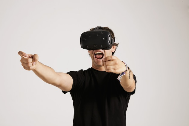 Emotional young gamer in vr headset and black unlabeled t-shirt screams while playing a game