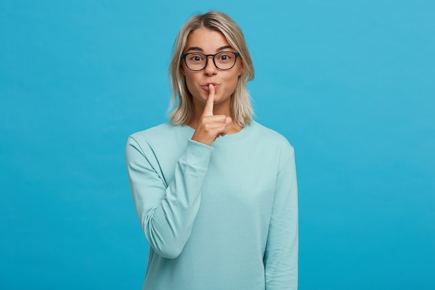 Эмоциональная молодая девушка в очках призывает к тишине