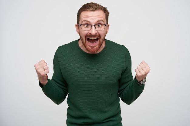 Эмоциональный молодой красивый бородатый мужчина с каштановыми короткими волосами, поднимающий кулаки и громко кричащий с широко открытыми глазами и открытым ртом, изолирован