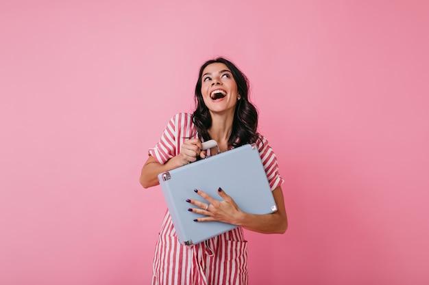 レトロな縞模様のドレスを着た感情的な若い女性は、お金で青いスーツケースをしっかりと持って、夢のように見上げます。