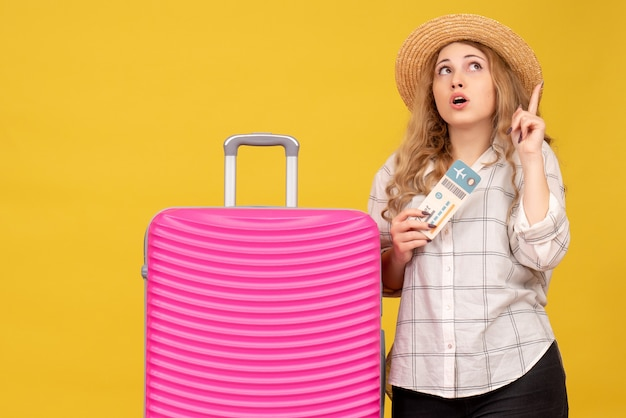 Эмоциональная молодая дама в шляпе показывает билет и стоит рядом со своей розовой сумкой, указывая вверх