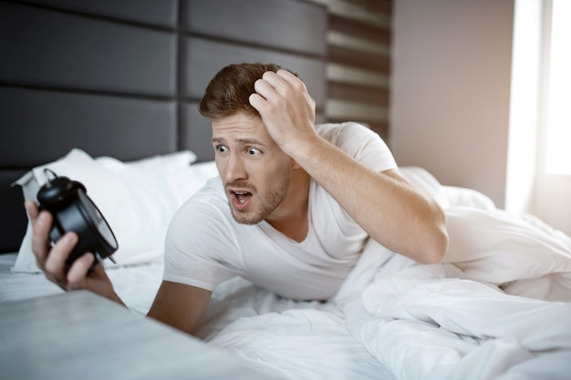 Emotional young man on bed in early morning. he overslept. guy hold clock and look at it scared.