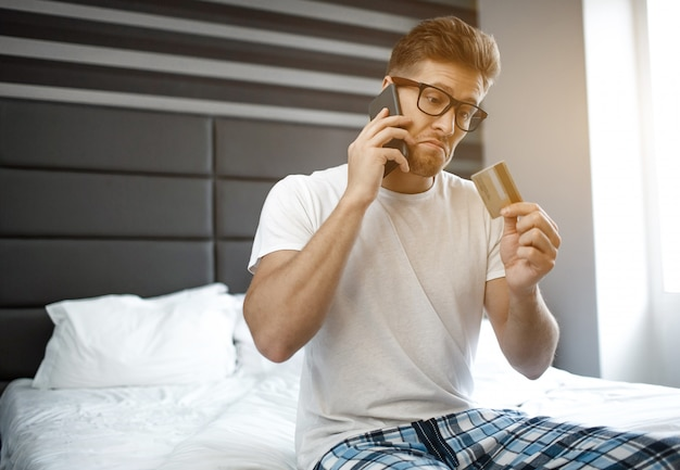 Emotional young man on bed early morning. he talk on phone and look at credit card in hand. guy wear pajama. daylight.