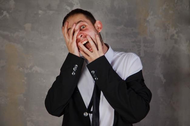 スーツを着た感情的な若い男は、灰色のテクスチャ背景に恐怖と恐怖を描いています。人のジェスチャーは恐怖とヒステリーについて話します、それは彼にとって不快です。人間の感情の概念。コピースペース