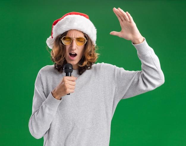 クリスマスのサンタの帽子と黄色いメガネを身に着けている感情的な若い男は、緑の背景の上に立っている腕を上げてマイクに向かって叫んでいます